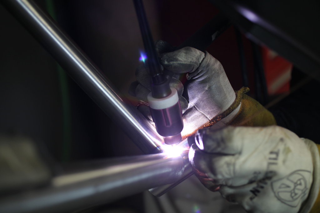 Here's a close-up of TIG welding the down tube to the bottom bracket shell. For the geeks, TIG stands for Tungsten Inert Gas. The brightly glowing electrode is the tungsten, which provides the arc. The inert gas is argon, which after emerging from the pinkish colored gas lens forms a protective cloud (invisible) around the […]
