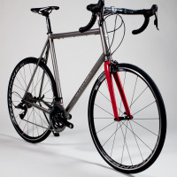 A very tall Custom Blend titanium road bike with Sram Red, a painted Enve fork and Hed wheels.